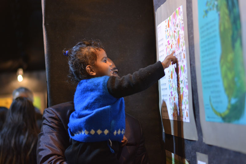 A toddler enjoying a colourful illustration of our poem poster 'Fugga' displayed at our stall